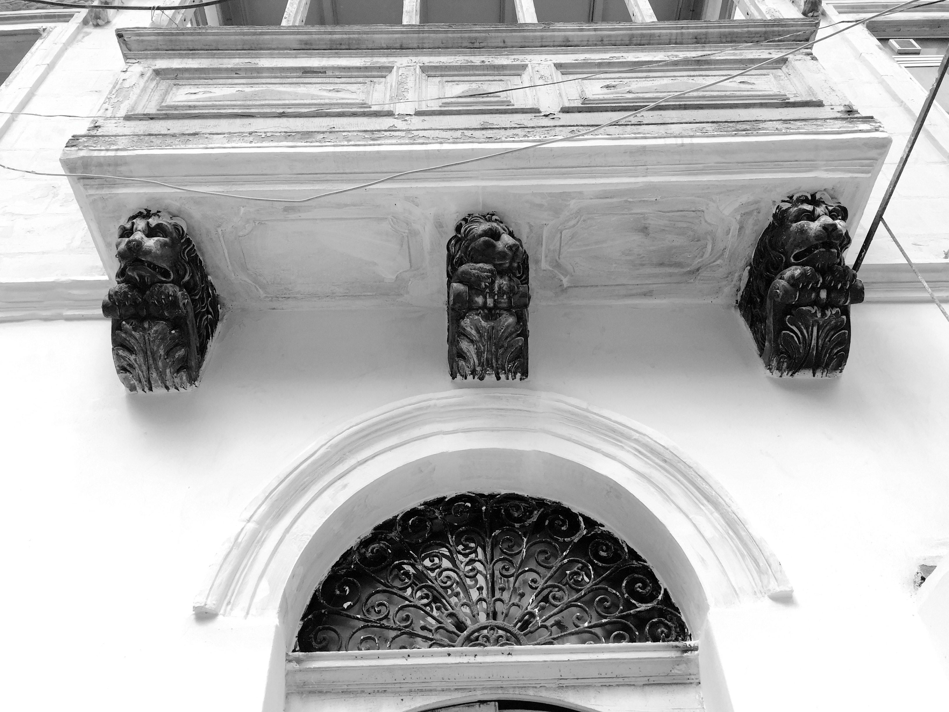 Timber balcony decor: lions and caryatides